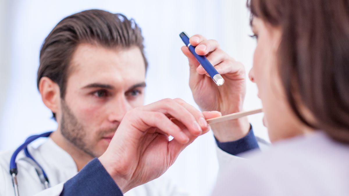 Ein Arzt nimmt einen Rachenabstrich bei einer Patientin vor.