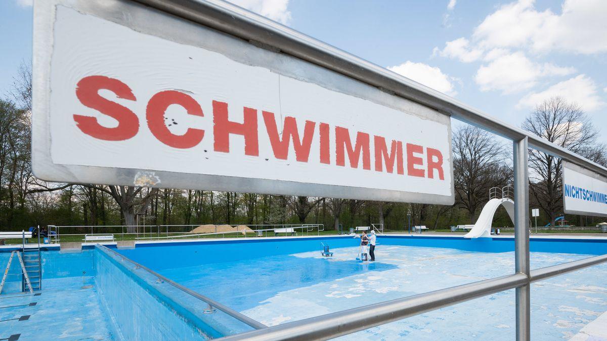 Helfer streichen ein Schwimmbecken von einem Freibad. Der Beginn der Freibadsaison in diesem Jahr steht coronabedingt noch nicht fest.