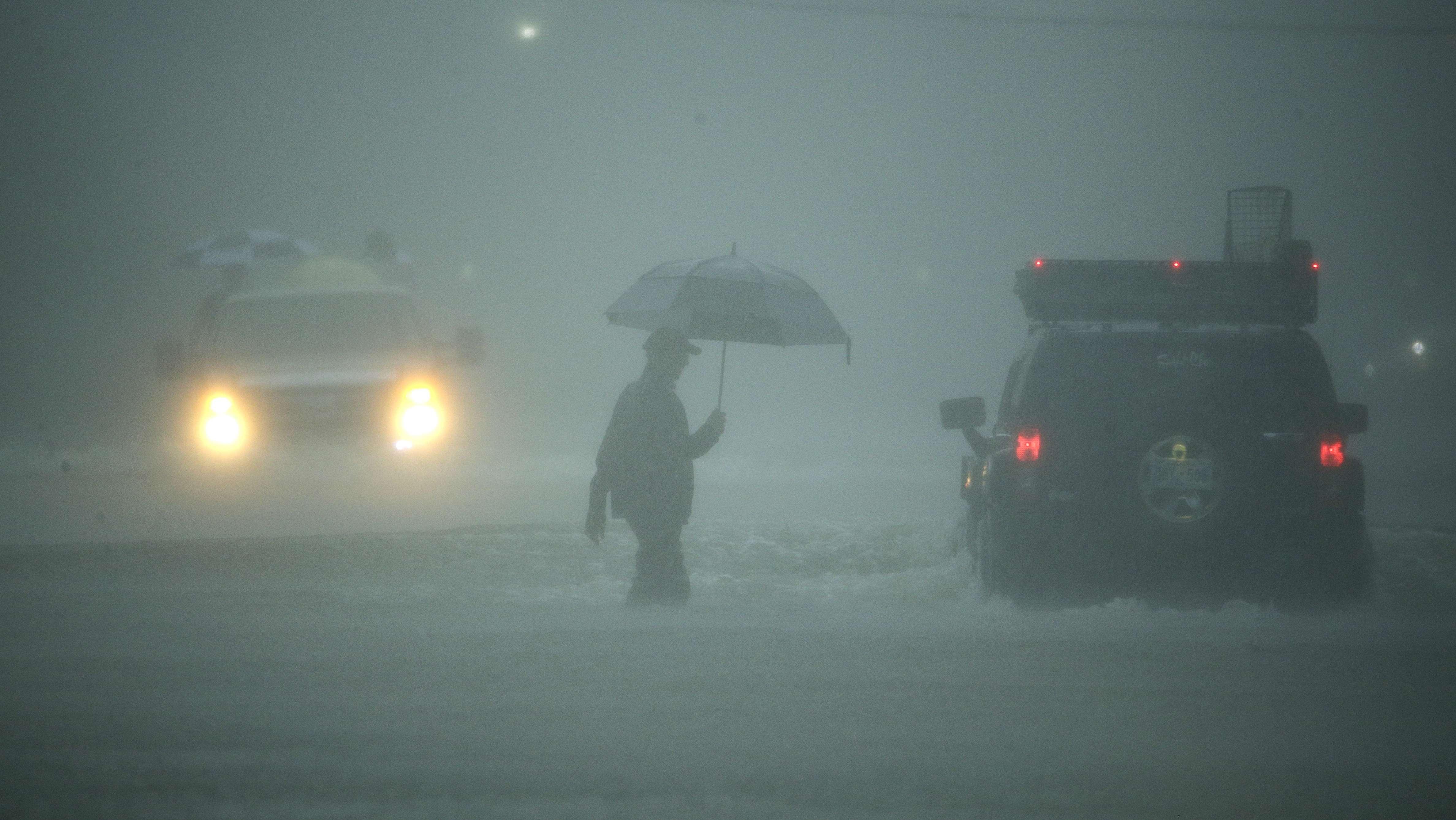 Ein Mann mit Regenschirm und zwei Autos auf einer überschwemmten Straße während des Hurrikans Harvey in Houston, Texas 2017