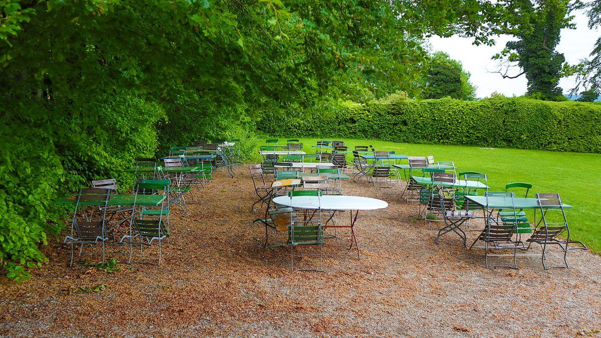 Schräg gegen die Tische gelehnte Stühle in einem leeren Biergarten