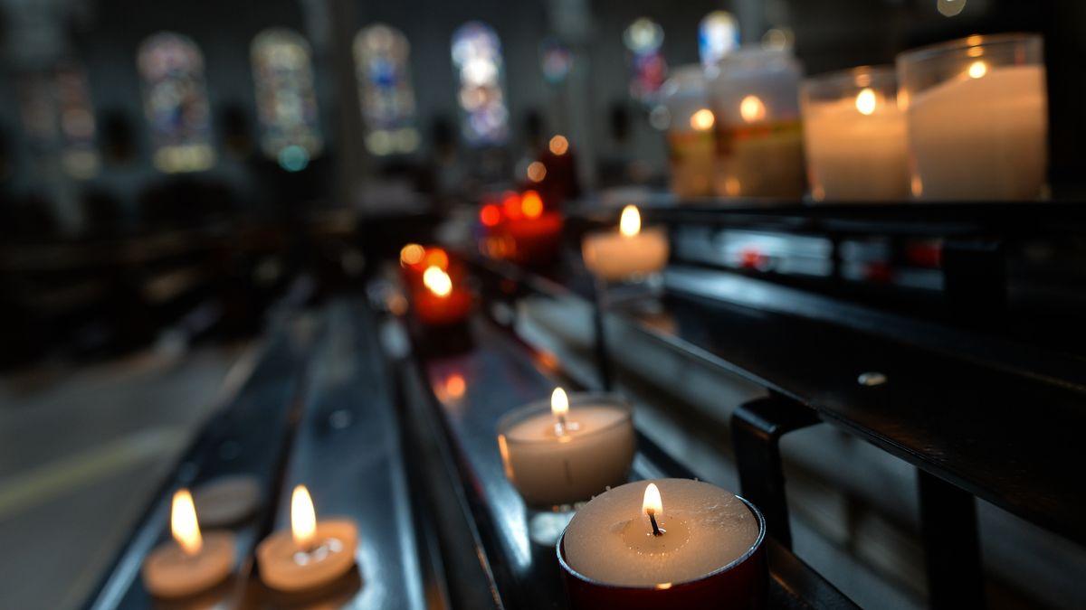 Kerzen zum Gedenken an Verstorbene in einer Kirche