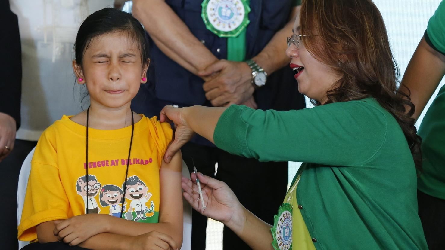 Philippinen, Manila: Die damalige philippinische Gesundheitsministerin Janette Garin (r) impft ein Mädchen gegen die Tropenkrankheit Denguefieber.