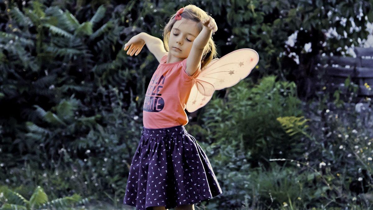 Man sieht ein kleines Mädchen mit Schmetterlingsflügeln auf dem Rücken tanzen.