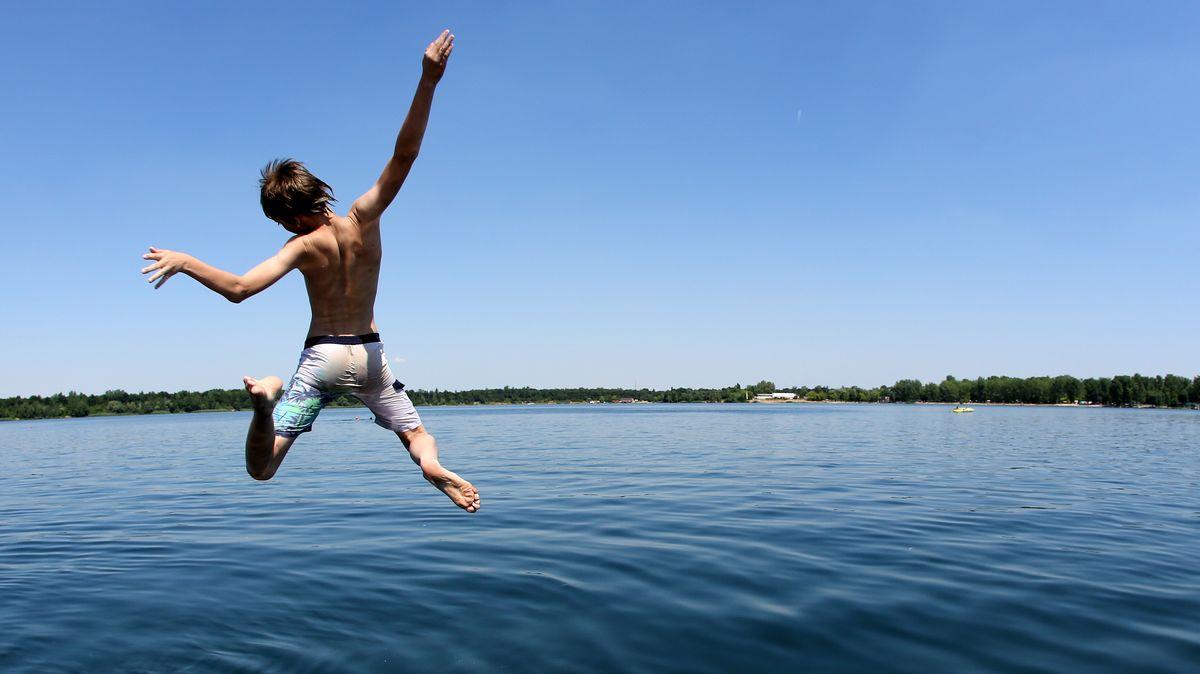 Ein Junge springt in einen Badesee