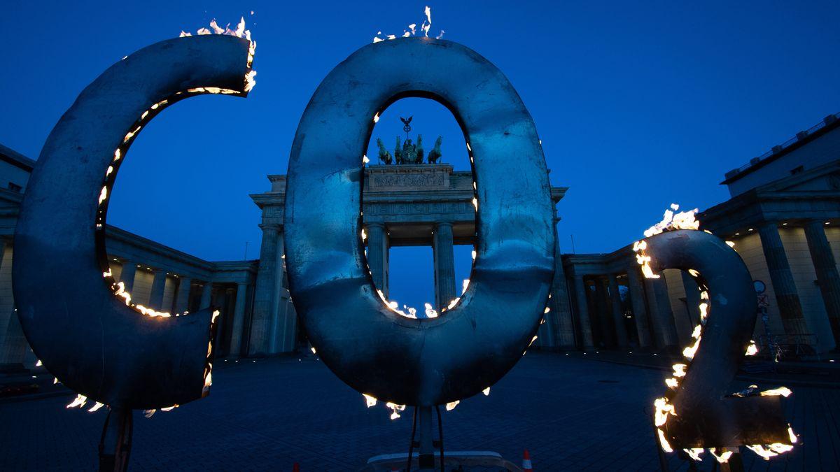 Bei einer Greenpeace-Aktion steht ein CO-2 Schriftzug vor dem Brandenburger Tor, aus dem Flammen schlagen. Mit der Aktion fordern Aktivisten der Umweltschutz-Organisation Greenpeace am 6. Mai 2021 die Bundesregierung auf, den CO-2 Ausstoß in Deutschland weiter zu reduzieren und auf die Einhaltung der Ziele des Weltklimagipfels von Paris zu achten.