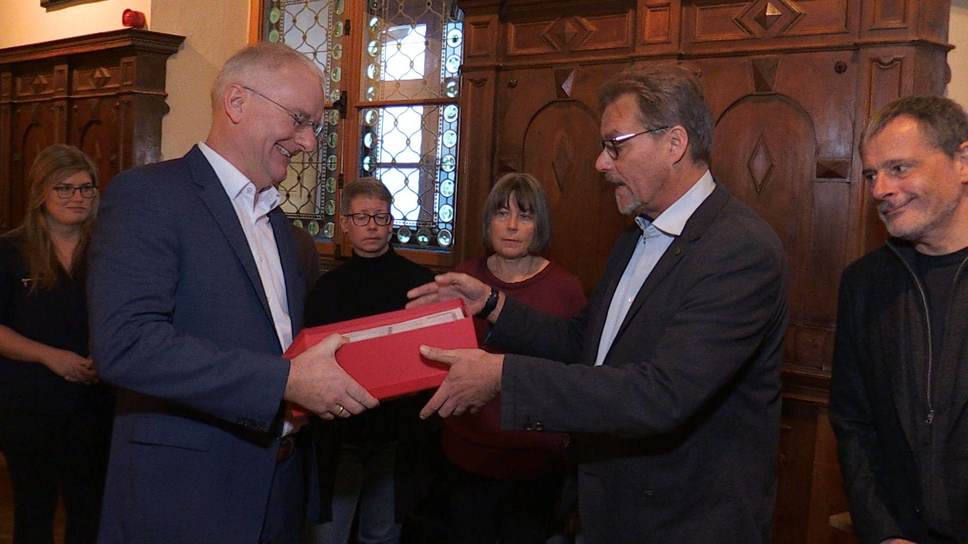 Übergabe der Unterschriften an OB Alexander Putz (links).