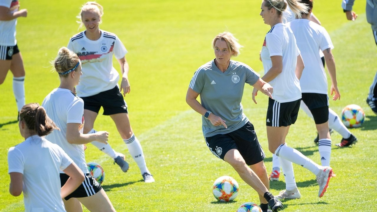 Martina Voss-Tecklenburg (M), Trainerin der deutschen Frauen-Nationalmannschaft, spielt mit einem Ball.