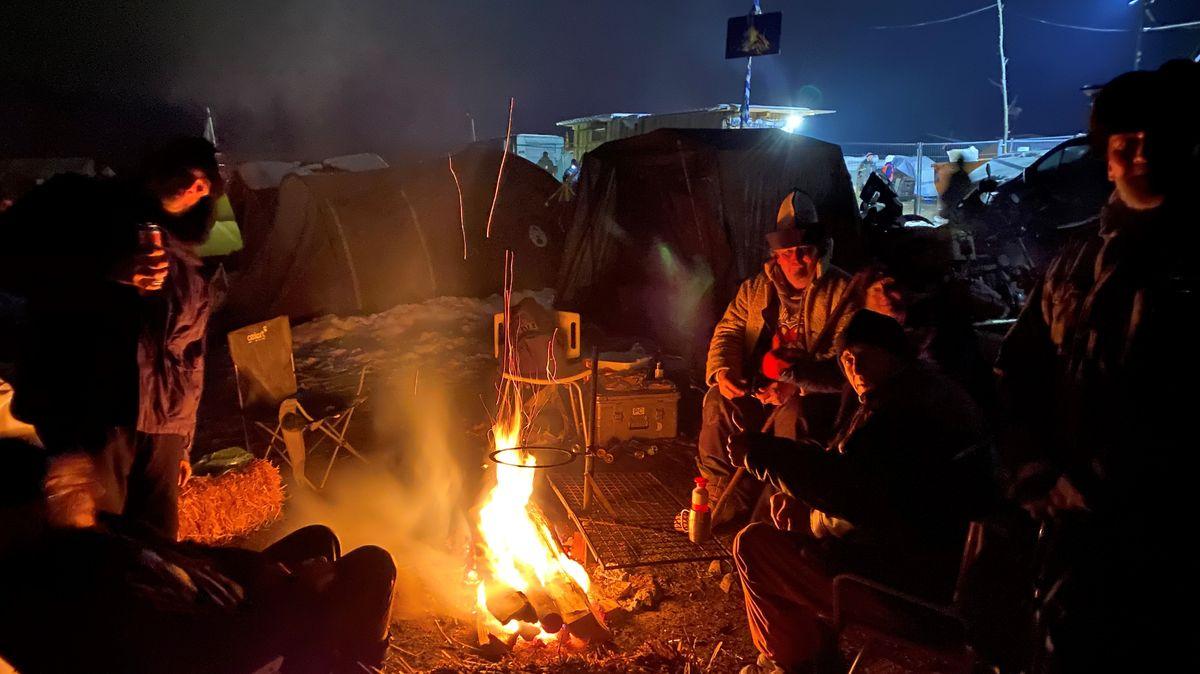 Die Camper sitzen im Dunkeln um ein Lagerfeuer