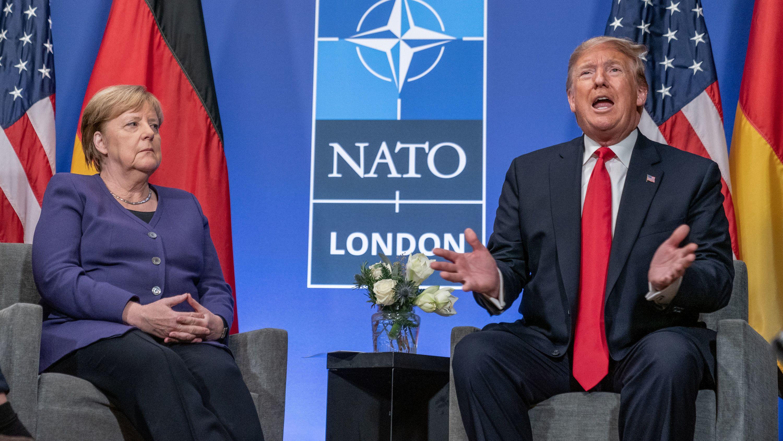 US Präsident Donald Trum, sitzt neben Bundeskanzlerin Angela Merkel (CDU) zu Beginn eines Bilateralen Gesprächs nach der Arbeitssitzung des Nato Gipfels.