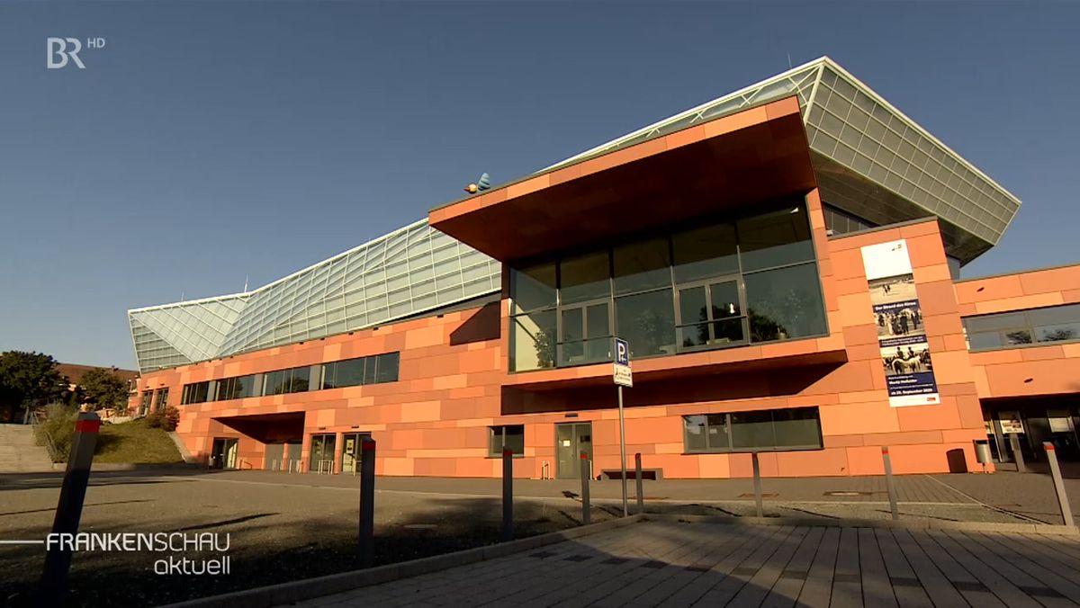 Die Fassade der Freiheitshalle ist rötlich, darüber das Dach mit spektakulären Glaselementen.