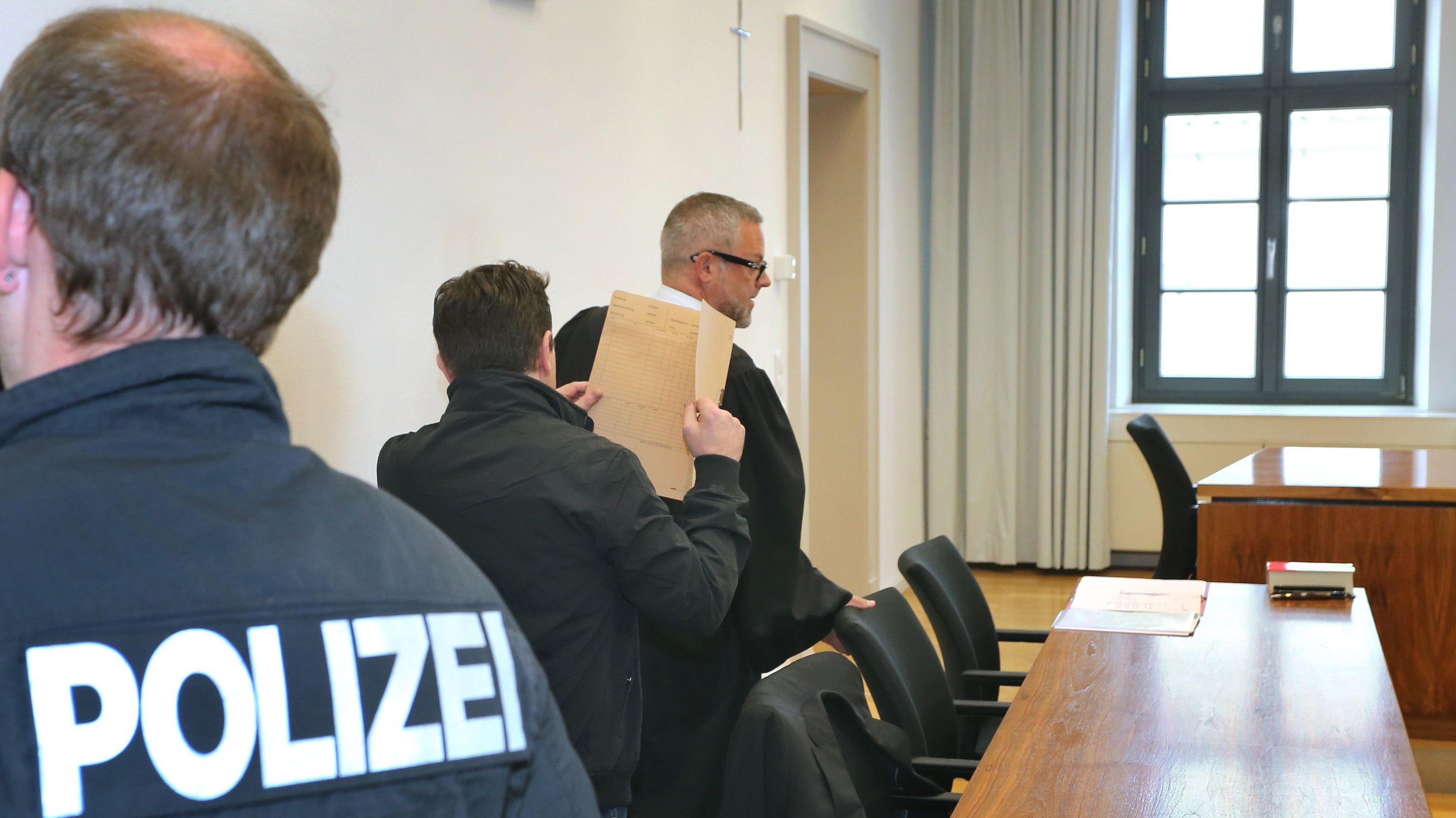 Der Angeklagte (Mitte) betritt mit seinem Anwalt den Verhandlungssaal im Landgericht Memmingen und hält sich einen Aktendeckel vor das Gesicht.