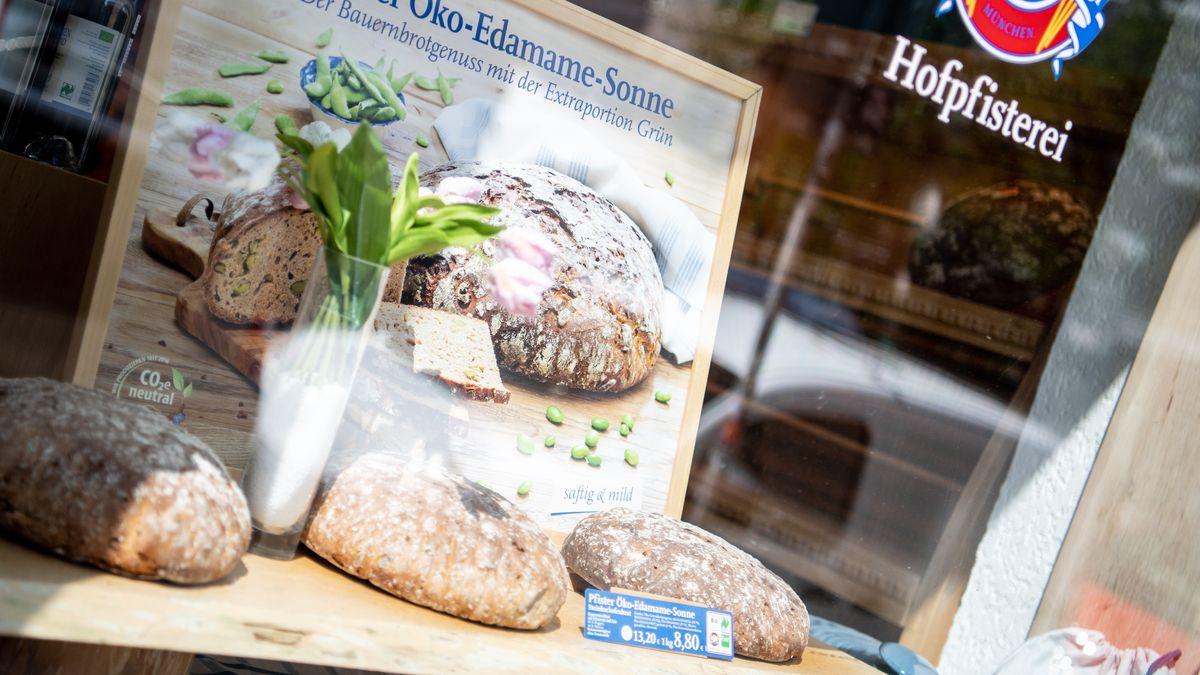 """Der Schriftzug """"Pfister Öko-Edame-Sonne"""" ist auf einer Werbetafel in einer Bäckerei-Filiale der Hofpfisterei hinter ausgestellten Sonnen-Broten zu sehen."""