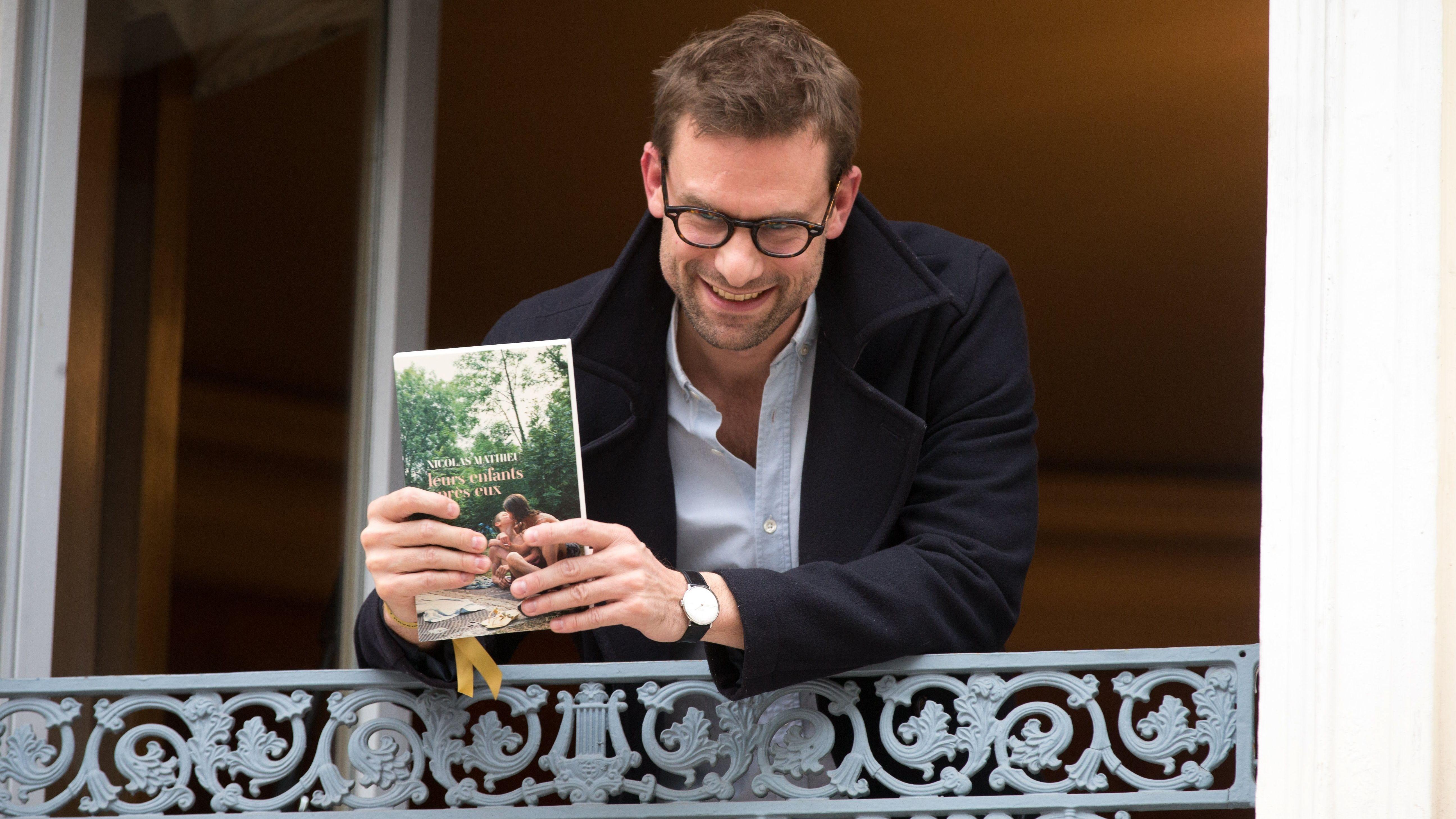 Ein zufriedener Nicolas Mathieu steht an einem offenen Fenster und hält seinen Roman in der Hand