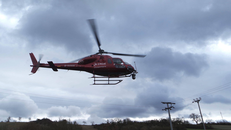 Hubschrauber fliegt über Strommasten