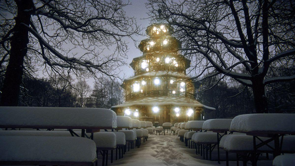 Der beleuchtete Chinesische Turm im Englischen Garten in München im Winter bei Schnee