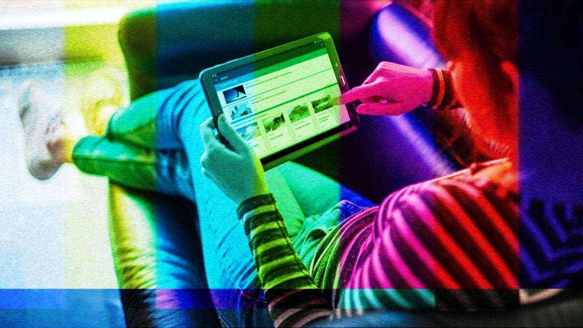 Eine Frau sitzt auf einem Sofa und hat ein kleines Tablet in der Hand.