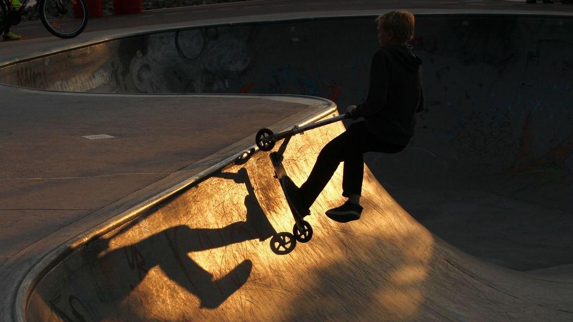 Junge mit einem Stuntscooter im Skatepark