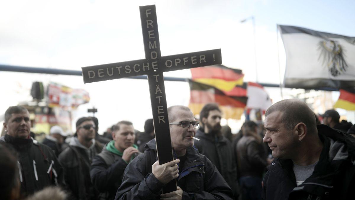 """03.10.2018, Berlin: Ein Teilnehmer der rechtspopulistischen Demonstration """"Tag der Nation"""" des Bündnisses """"Wir für Deutschland"""" trägt ein Kreuz mit der Aufschrift """"Fremde Täter - Deutsche Opfer!"""""""