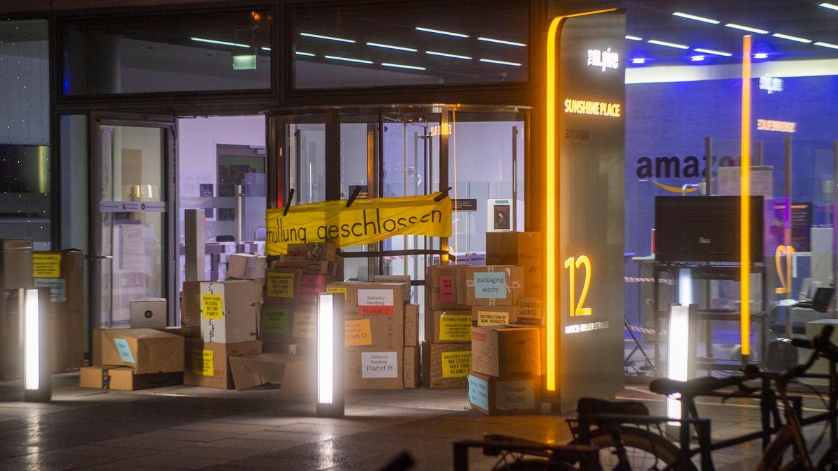 Leere Pakete mit aufgedruckten Vorwürfen stapeln sich am Eingang des Internetversandhauses von Amazon in München