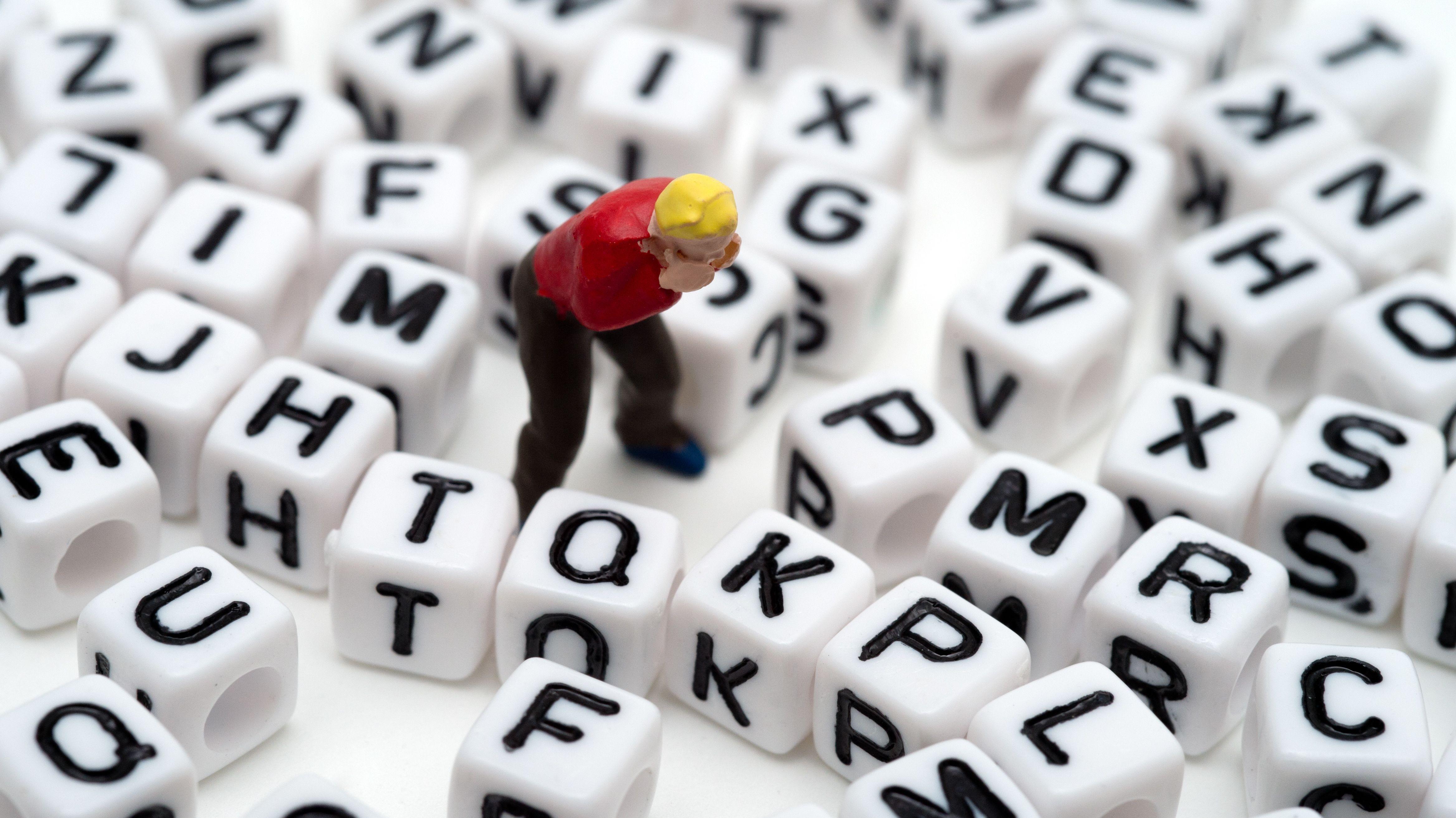 Figur eines verzweifelten Mannes steht in Berlin zwischen verschiedenen Buchstabenwürfeln