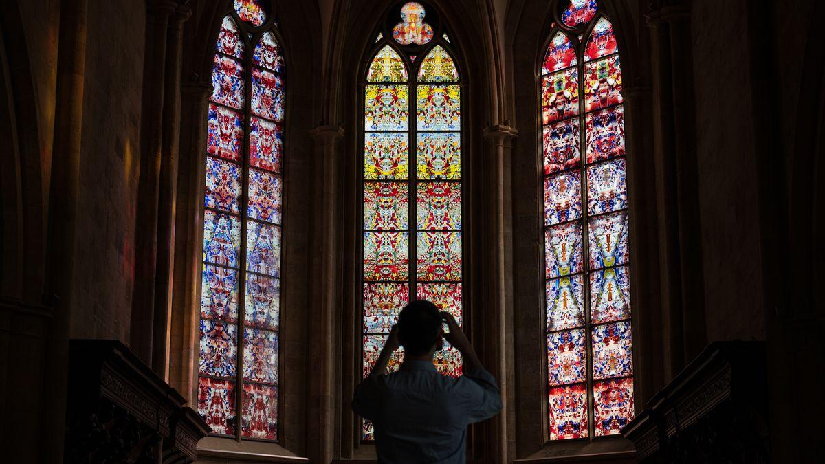 Ein Mann steht vor bunten Kirchenfenstern.
