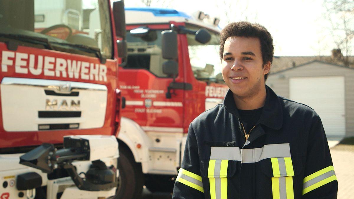 Ein angehender Abiturient steht vor einem Feuerwehrauto.