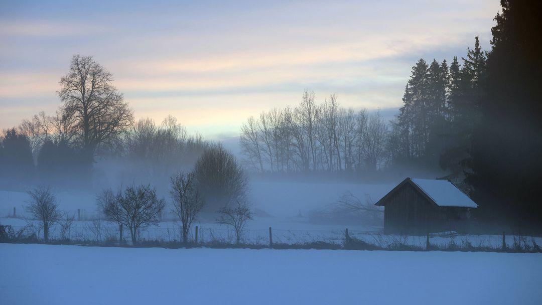 23.01.2021, Bayern, Bad Wörishofen: Nebel liegt im Sonnenuntergang über der schneebedeckten Landschaft.