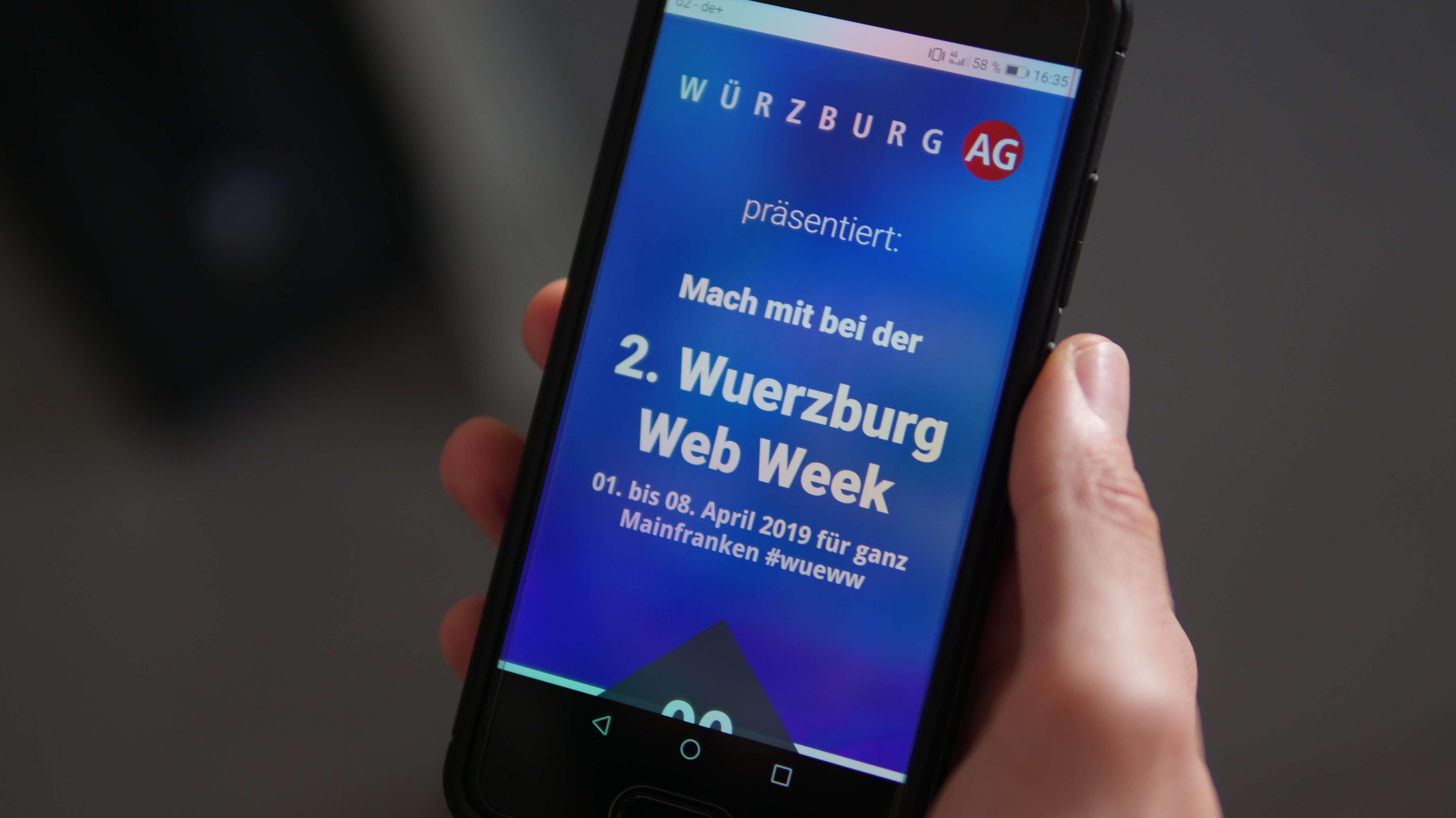 Foto eines Smartphones, auf dem die Seite der Würzburg Web Week aufgerufen ist.
