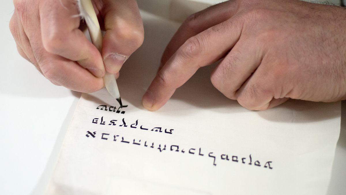 Ein Rabbiner beschriftet eine Thora-Rolla.