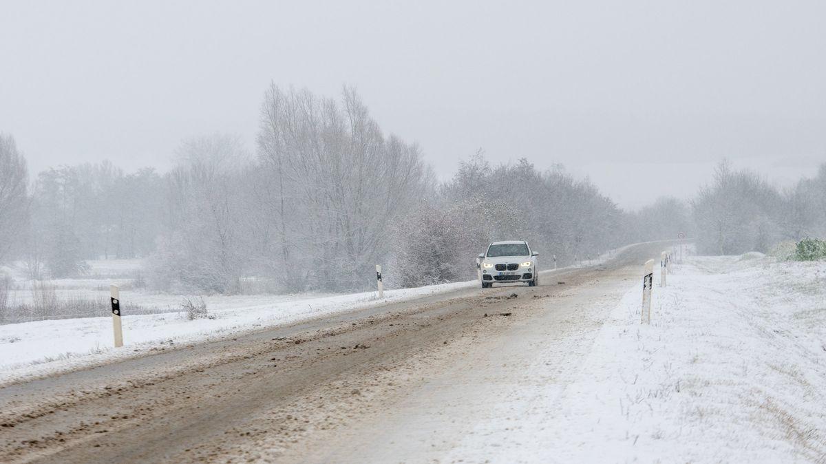 Symbolbild: Ein Auto fährt bei Dattenhausen in Bayern über eine verschneite Straße.