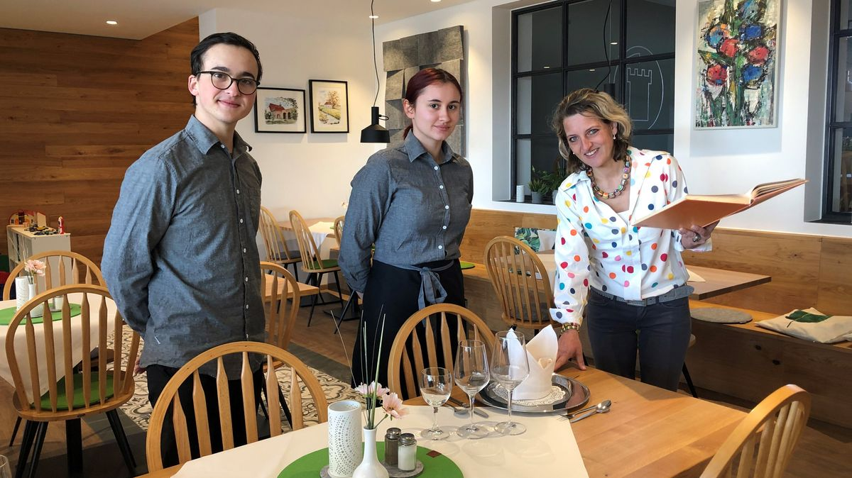 Hotelchefin deckt mit zwei Lehrlingen den Tisch fachgerecht ein