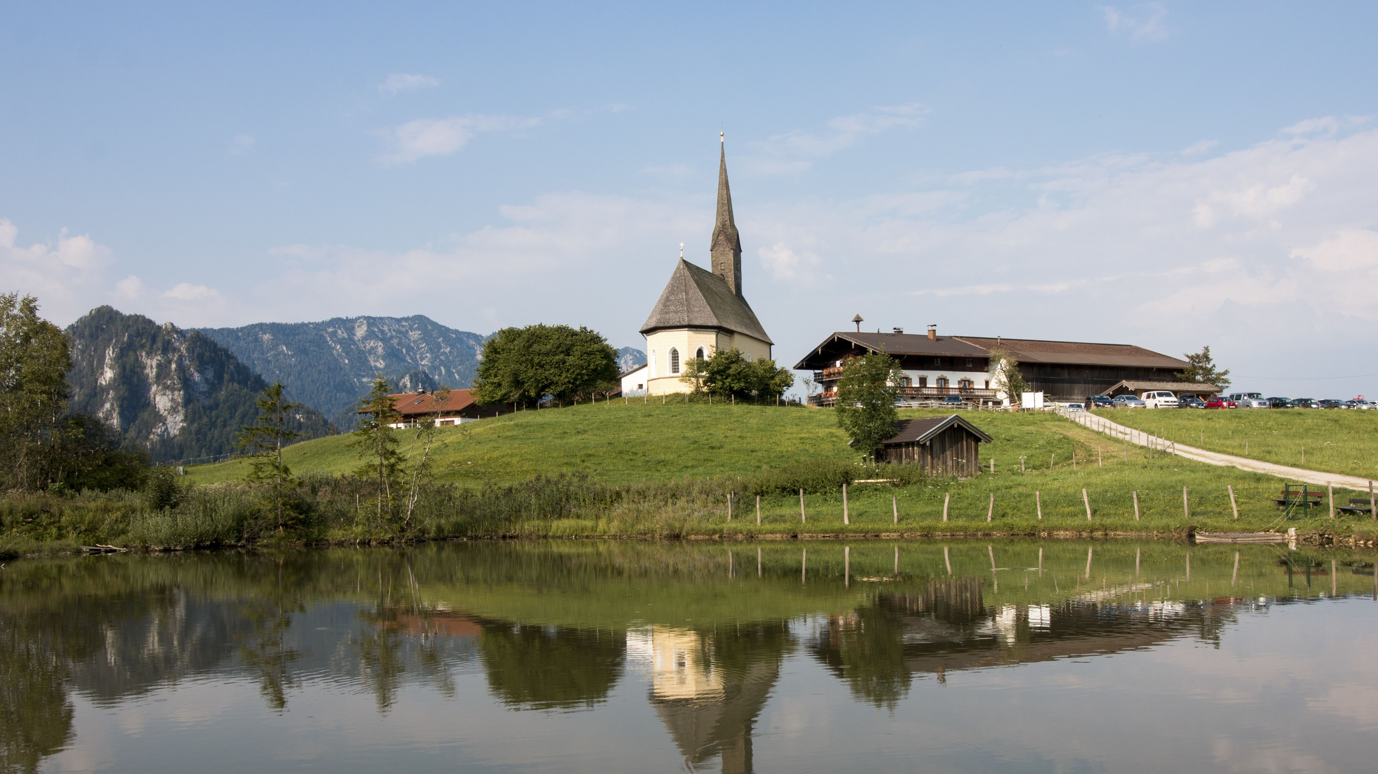 Blick auf die kleine Nikolauskirche in Einsiedl in Inzell mit Weiher im Vordergrund
