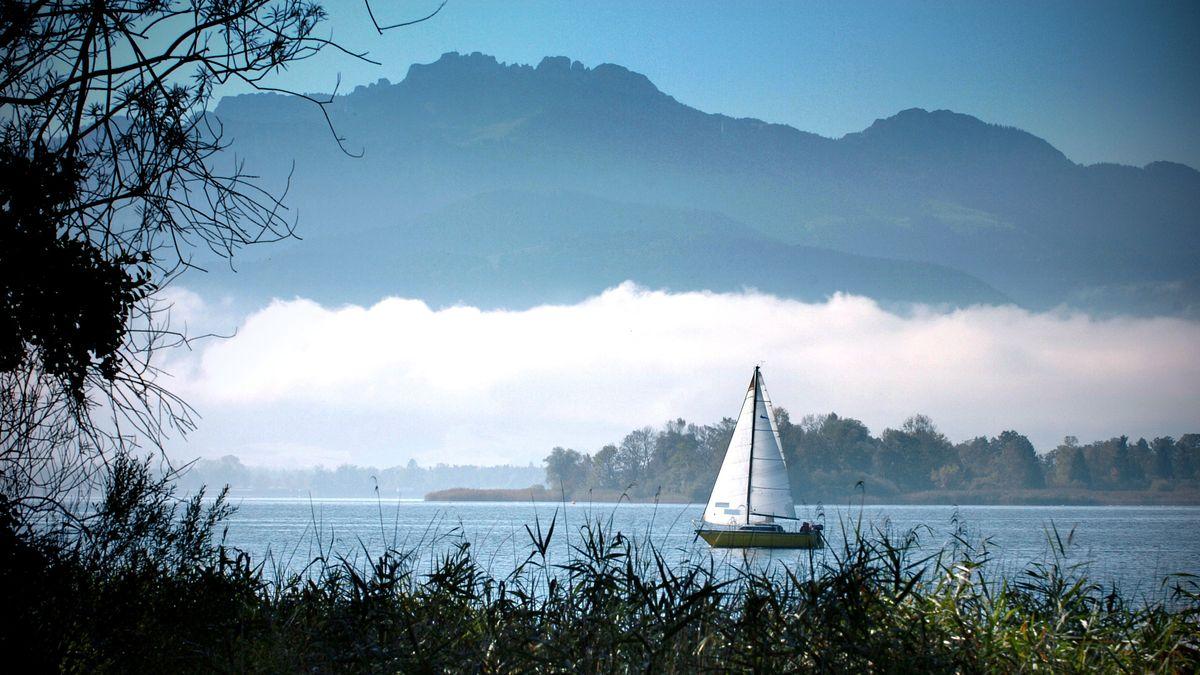 Die Kampenwand hinter dem Chiemsee, auf dem ein Segelboot fährt.