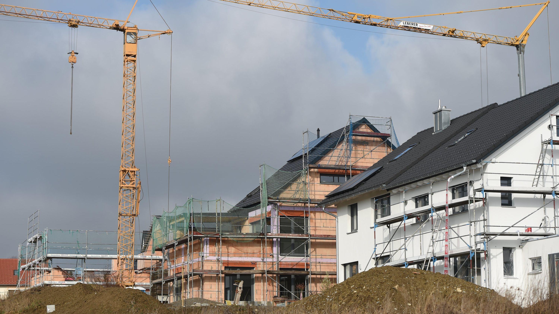 Mehrere Häuser im Rohbau stehen in einem neuen Wohnviertel.