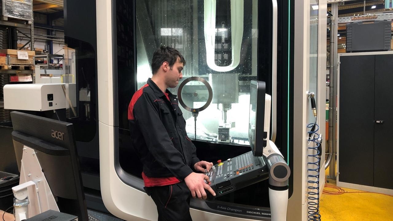 Ein Auszubildender probiert eine automatische Fräsmaschine aus.