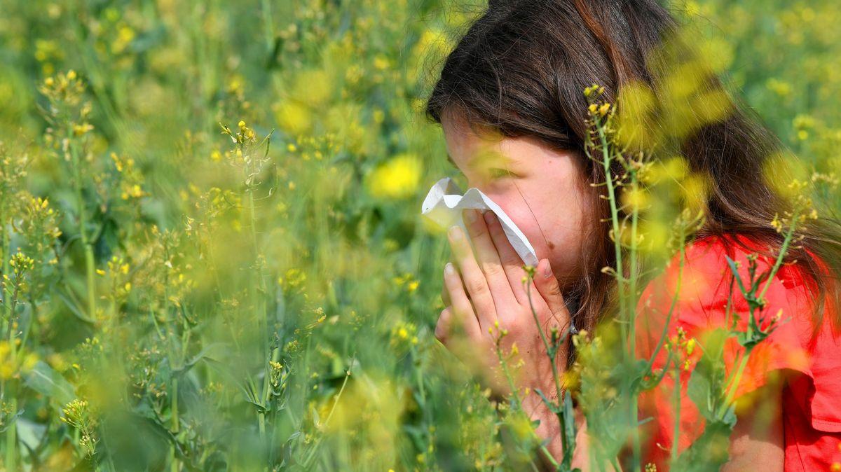 Eine Frau schnäuzt sich auf einer Wiese die Nase.