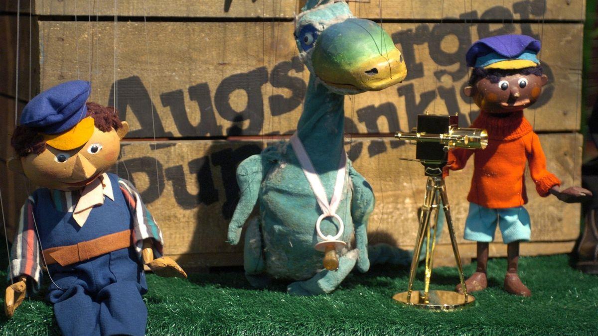 Drei Marionetten: Ein blaubekleideter Lokomotivführer, ein grüner Dino und ein kleiner schwarzer Junge in rotem Pulli mit Kappe: Lukas der Lokomotivführer, Urmel und Jim Knopf