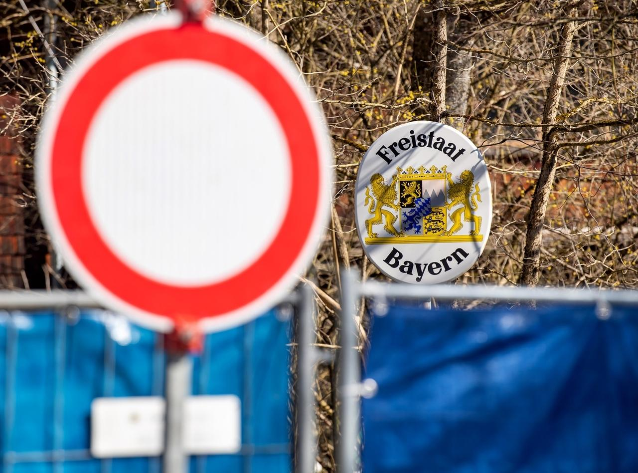 """Bayern, Aschau Im Chiemgau: Ein """"Durchfahrt verboten""""-Schild steht vor einem Bauzaun, der mit blauer Plane die Grenze zwischen dem Aschauer Ortsteil Sachrang auf bayerischer Seite und Niederndorferberg im Kufsteinerland in Tirol (Österreich) abgesperrt."""