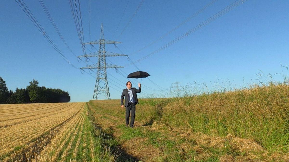 Unter dieser Stromleitung in Niederaichbach bekommen Spaziergänger leichte Stromschläge. Ein Regenschirm schützt.