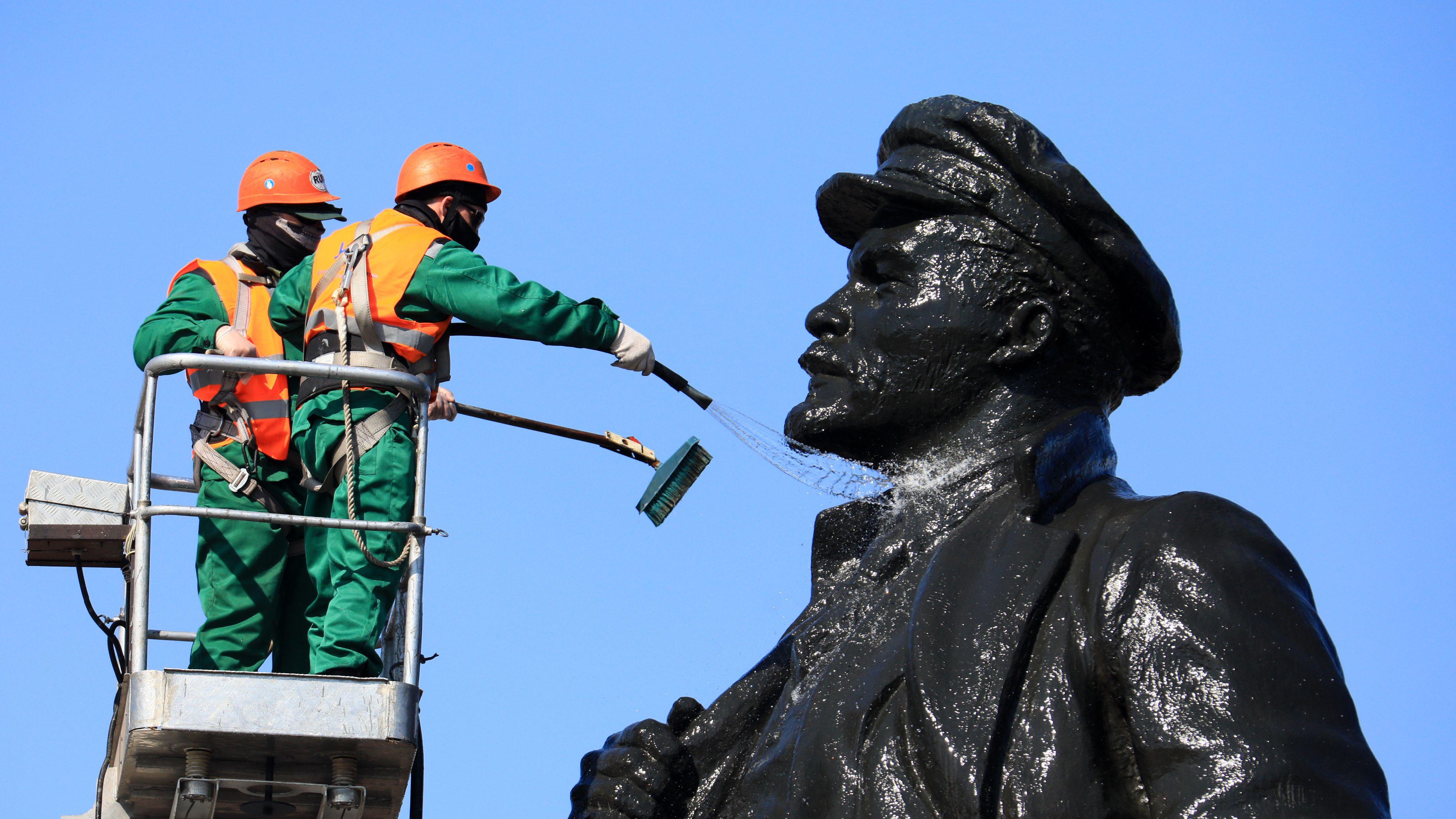 Das Bild zeigt zwei Arbeiter beim Reinigen einer Leninstatue im russischen Krasnojarsk.