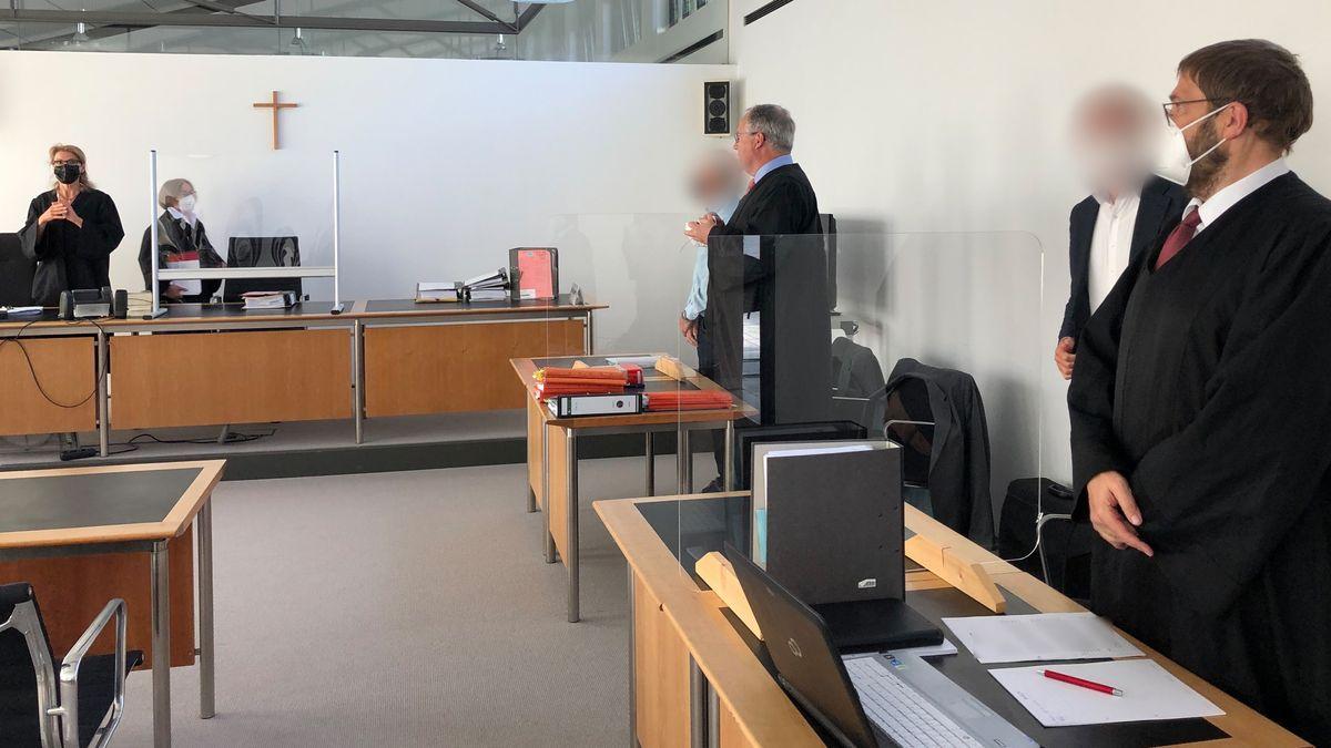 Die Angeklagten (2.v.r. und 4.v.r.) stehen mit ihren Verteidigern vor dem Start der Verhandlung im Gerichtssaal des Amtsgerichts.