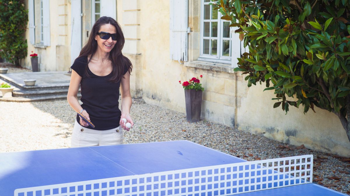 Eine Frau spielt draußen Tischtennis.