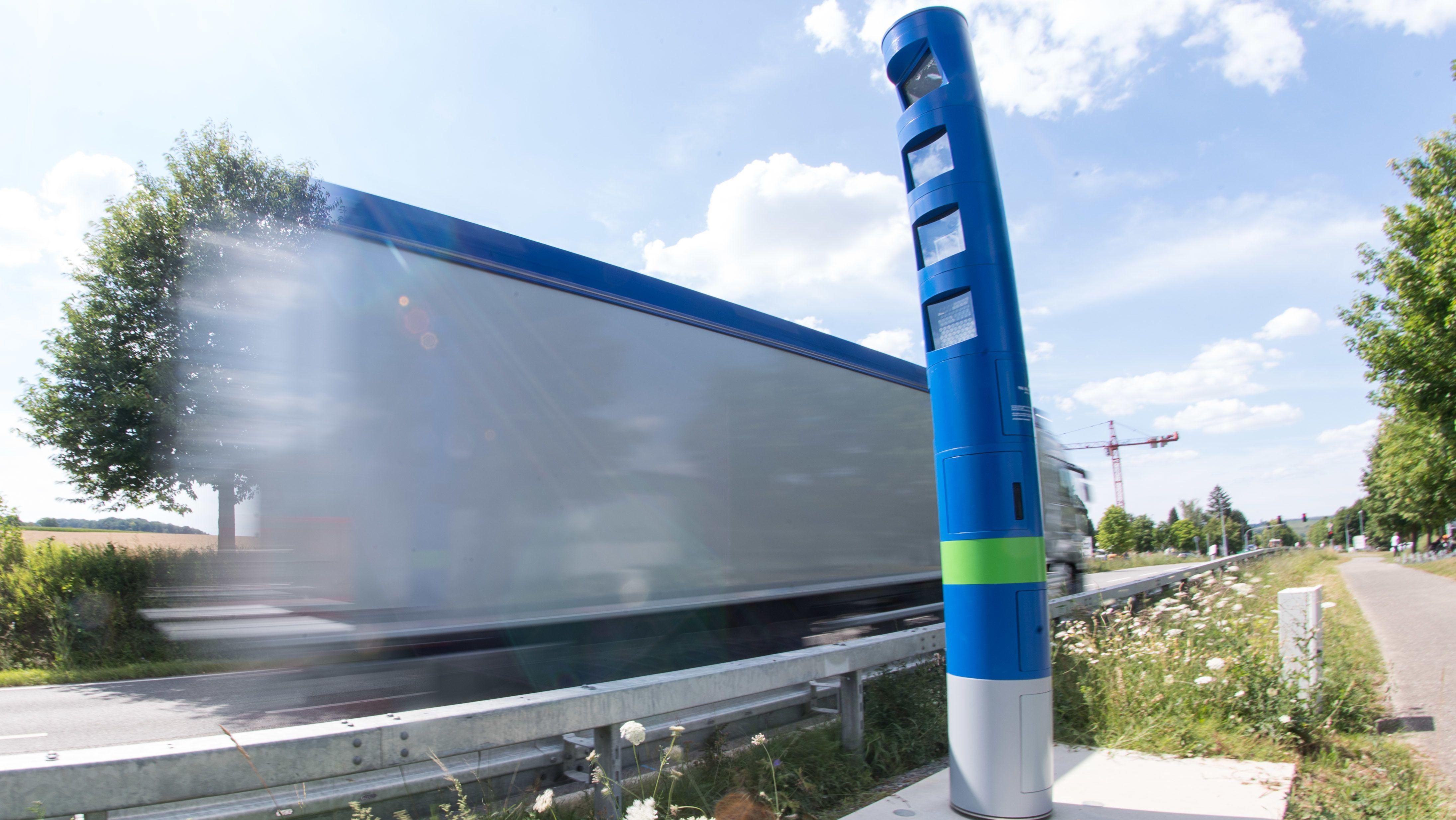 Ein Lastwagen fährt an einer Mautsäule auf einer Bundesstraße vorbei (Wischeffekt durch Langzeitbelichtung).