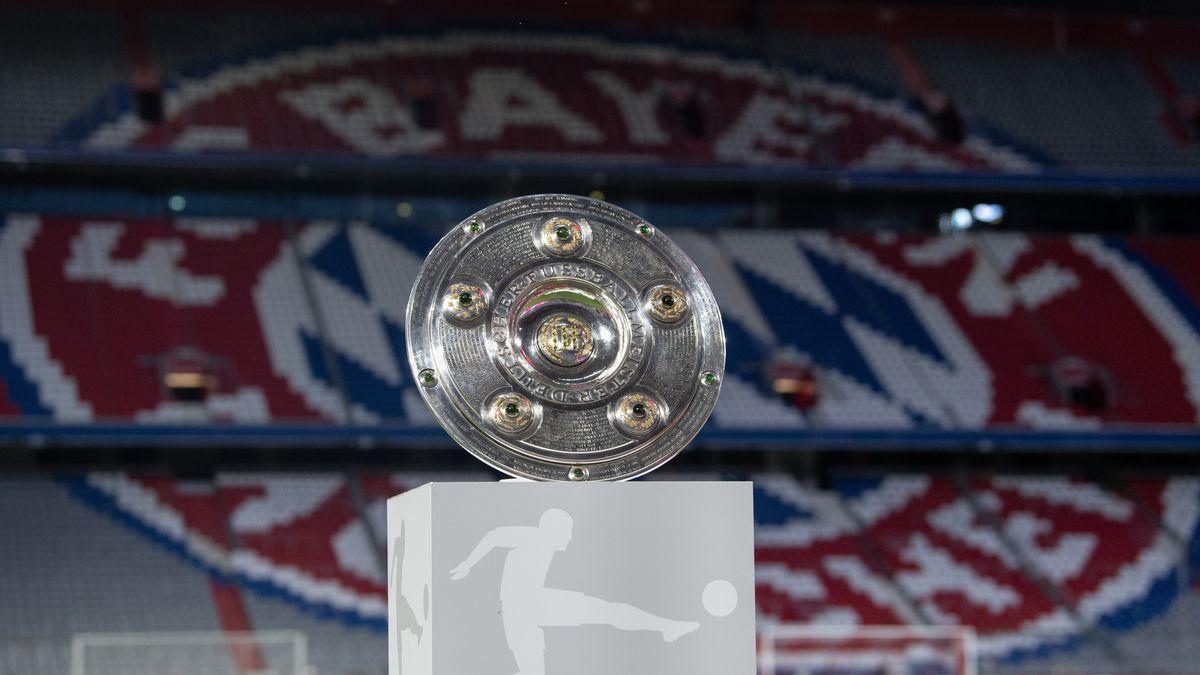Die Meisterschale vor dem Wappen des FC Bayern