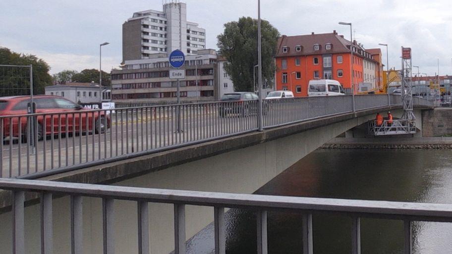 Männer mit grellen orangefarbenen Mänteln stehen auf einem Gerüst unterhalb der Gänstorbrücke zwischen Neu-Ulm und Ulm