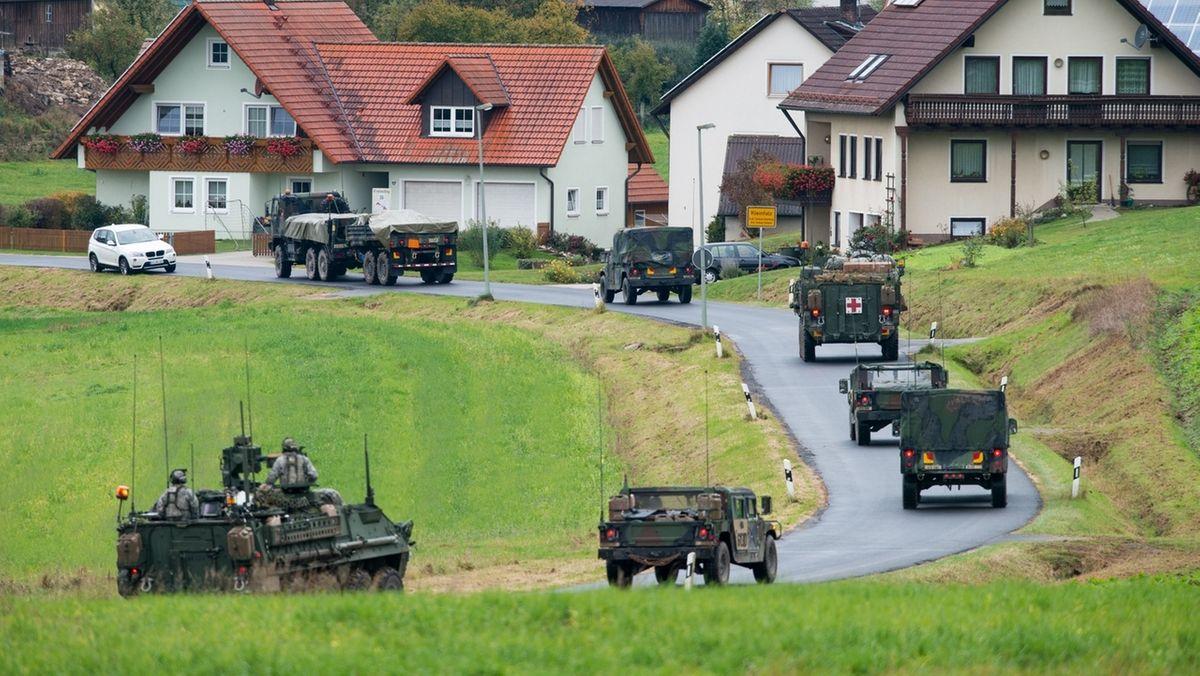 ARCHIV - 15.10.2012, Bayern, Kleinfalz: Militärfahrzeuge der US-Armee fahren durch den Ort Kleinfalz nahe dem Truppenübungsplatz Grafenwöhr.