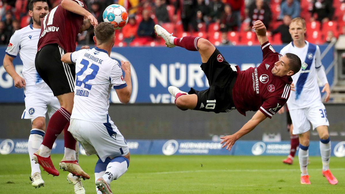 Die Nürnberger Nikola Dovedan (r) und Erik Shuranov (l) kämpfen mit dem Karlsruher Christoph Kobald (M) um den Ball.