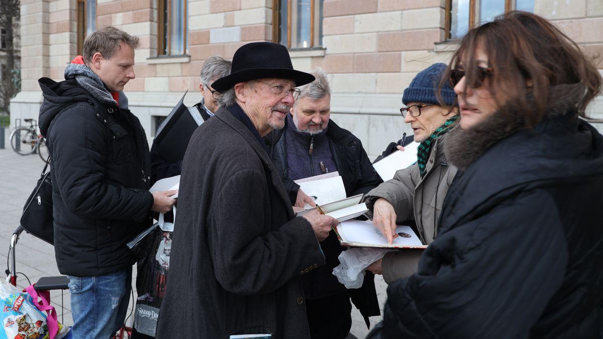 Der Schriftsteller Peter Handke gibt vor dem Hotel in Stockholm Autogramme und signiert seine Bücher