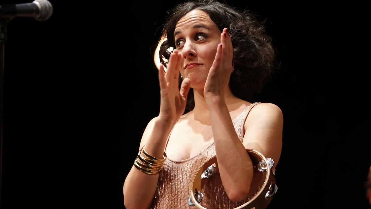 Lisa Bassenge bei einem Liveauftritt, klatschend mit Schellenkranz um den Arm