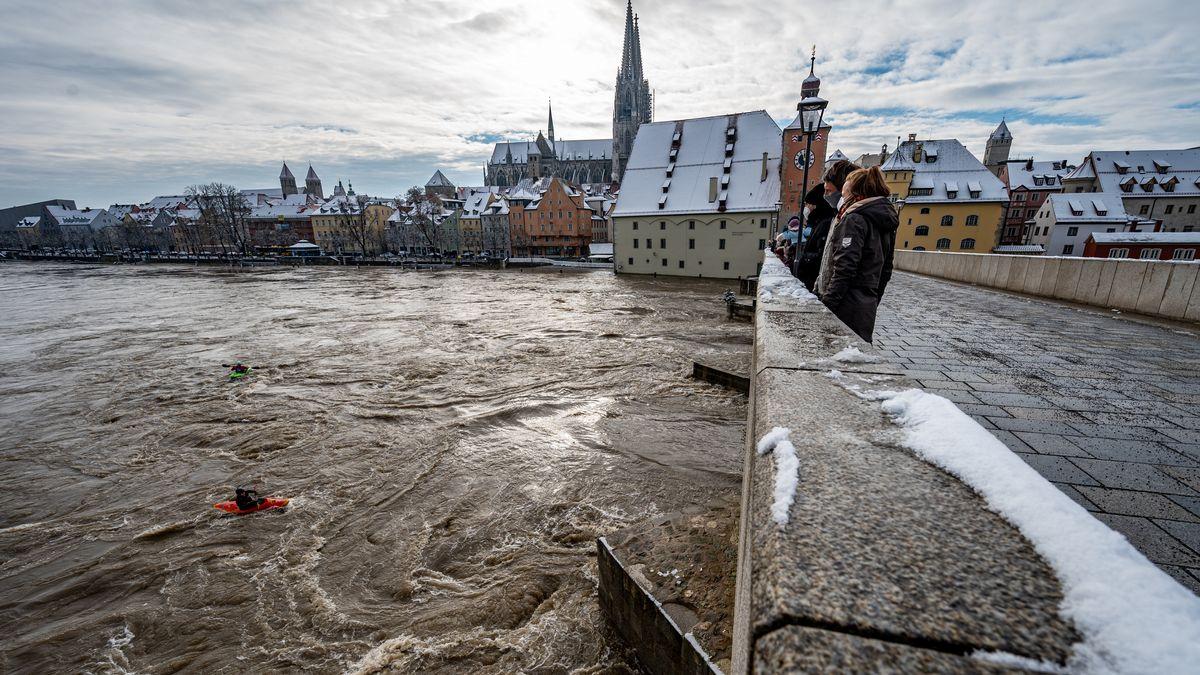 Kajakfahrer sind an der Steinernen Brücke auf der Donau im Hochwasser unterwegs.